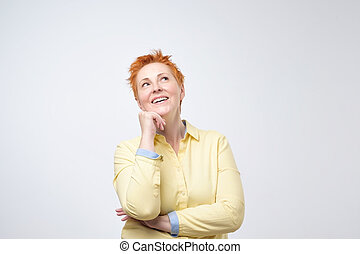 Happy thinking casual woman with red hairstyle dreaming looking up. She is planning her future.