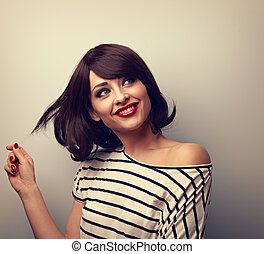 Happy thinking  flirting young woman with short hairstyle looking on empty blue copy space. Closeup portrait