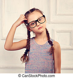 Happy thinking kid girl in fashion glasses and blouse with serious emotional face scratching the head on studio background. Toned portrait