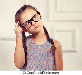 Happy thinking kid girl in fashion glasses and blouse with...