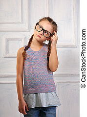 Happy thinking kid girl in fashion glasses and blouse with serious emotional face scratching the head on blue studio background