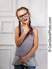 Happy thinking kid girl in fashion glasses with excited emotional face looking on blue studio background