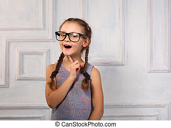 Happy thinking kid girl in fashion glasses with excited emotional face looking on studio background. Closeup portrait
