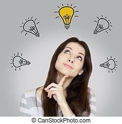 Happy thinking woman looking up on idea yellow bulb. Inspiration concept on grey background