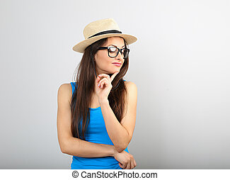 Happy thinking young woman looking in fashion glasses and straw hat on blue background
