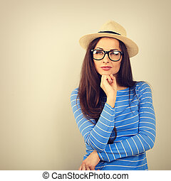 Happy thinking young woman looking up in fashion glasses and straw hat