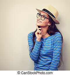 Happy thinking young woman looking up in fashion glasses and straw hat. Vintage toned portrait