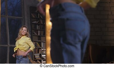Happy thinner woman in big jeans dancing at mirror - ...