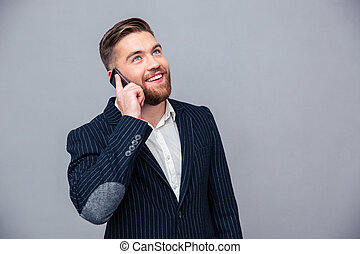Happy thoughtful businessman talking on the phone
