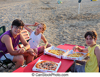 happy three brothers eating pizza on the beach