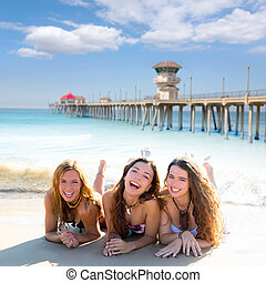 happy three friends girls lying on beach sand smiling -...
