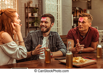 Happy three friends sharing a laugh and playing hedbanz together