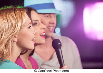 Happy three friends singing in microphones. two women and man having fun isolated in bar