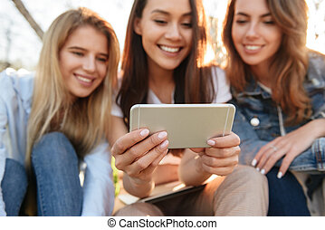 Happy three friends women using mobile phone.