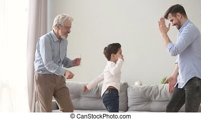 Happy three generations men family dancing having fun at...