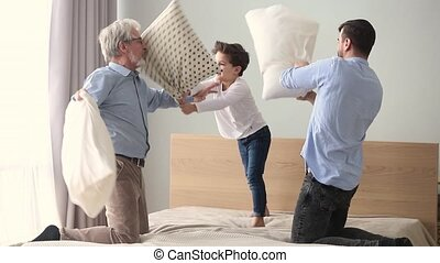 Happy three generations men family having pillow fight on...