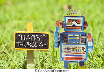 Happy Thursday word. Toy robot with sign on green grass.