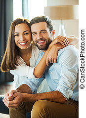 Happy to be together. Beautiful young loving couple sitting...