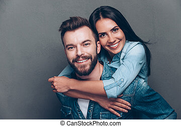 Happy to be together. Handsome young man piggybacking beautiful woman and smiling while standing against grey background