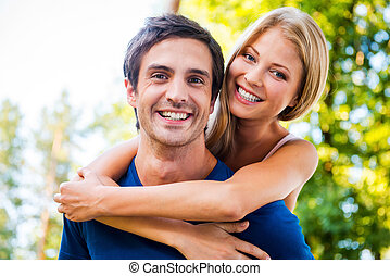 Happy to be together. Low angle view of beautiful young loving couple standing outdoors together while woman hugging her boyfriend and smiling
