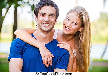 Happy to be together. Portrait of beautiful young loving couple smiling and looking at camera while standing outdoors