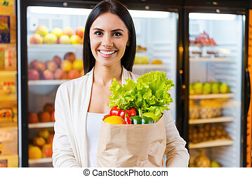 Happy to find everything I want. Beautiful young woman holding shopping bag with fruits and smiling while standing in grocery store near refrigerator