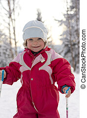 Happy toddler (2 years old) skiing in a beautiful winter landscape.