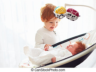 happy toddler baby brother welcoming his little baby sister, that lying in cradle swings