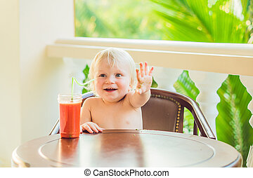 Happy toddler boy drinking healthy selfmade smoothie