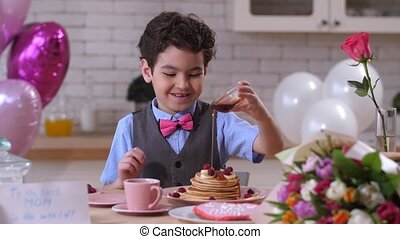 Happy toddler boy pouring maple syrup on pancakes - Smiling...
