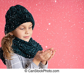 Happy toddler girl in a warm hat and scarf standing under Christmas snow, catching it, enjoying a miracle on a pink background.