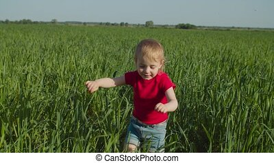 Portrait of joyful smiling adorable toddler girl learning to walk, making confident first steps in green wheat field, expressing positivity , happiness and enjoyment over beautiful natural landscape.