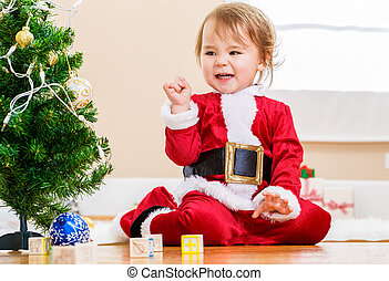 Happy toddler girl playing near the Christmas tree