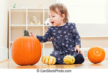 Happy toddler girl playing with pumpkins