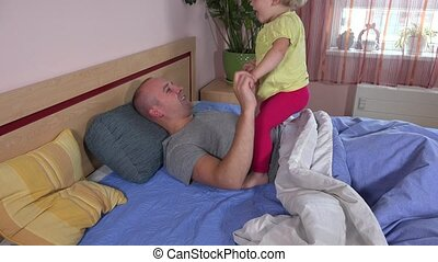 Happy toddler girl riding daddy on bed. Child enjoy time with father