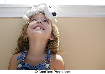 Happy toddler girl with toy dog over head - Happy toddler...