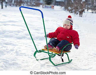 toddler on sled in winter