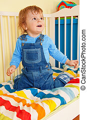 Happy toddler sitting in the baby cot