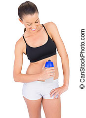 Happy toned woman in sportswear holding flask