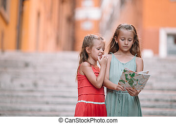 Adorable little girl looking at city map in roman streets in Italy. Happy toodler kids enjoy italian vacation holiday in Europe
