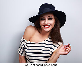 Happy toothy laughing makeup female model in black elegant hat with red brigh lipstick on blue background