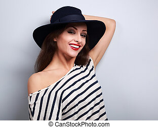Happy toothy smiling female model in black elegant hat on blue background