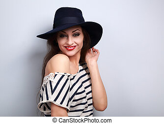 Happy toothy smiling makeup female model in black hat with red lipstick posing on blue background