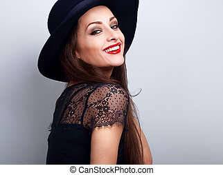 Happy toothy smiling makeup woman in black fashion hat with bright red lipstick on blue background