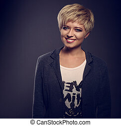 Happy toothy smiling young blond woman with short bob hair style looking in grey trendy jacket on dark background. Toned closeup portrait