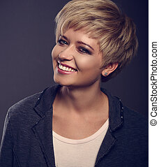 Happy toothy smiling young blond woman with short bob hair style looking in grey trendy jacket on dark background. Closeup toned portrait