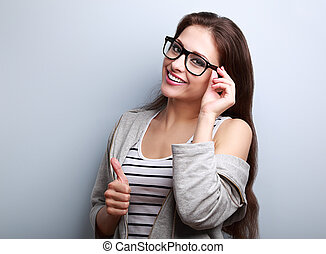 Happy toothy smiling young woman in glasses showing thumb up...