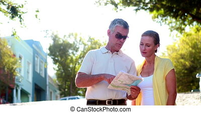 Happy tourist couple reading map an