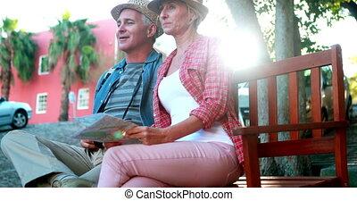 Happy tourist couple sitting on bench