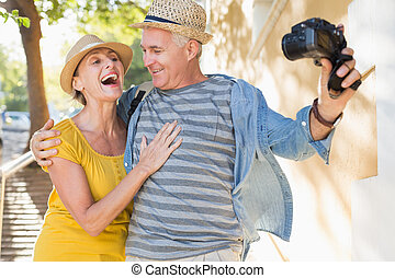 Happy tourist couple taking a selfie in the city on a sunny ...
